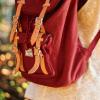 Foto mostra detalhe da mochila vermelha de um estudante